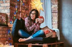 Menina bonita que aprecia a manhã de Natal que guarda uma caixa de presente ao sentar-se em um sofá em uma sala decorada com sótã imagens de stock royalty free