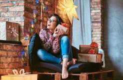 Menina bonita que aprecia a manhã de Natal que guarda uma caixa de presente ao sentar-se em um sofá em uma sala decorada com sótã fotos de stock