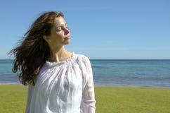 Menina bonita que aprecia o sol no oceano Fotos de Stock Royalty Free