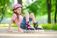 Menina bonita que aprende ao patim de rolo no dia de verão bonito em um parque fotos de stock