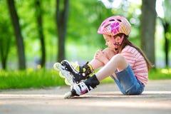 Menina bonita que aprende ao patim de rolo no dia de verão bonito em um parque foto de stock royalty free