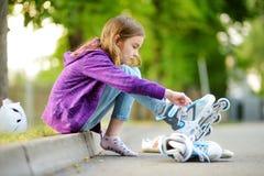 Menina bonita que aprende ao patim de rolo no dia de verão em um parque Capacete de segurança vestindo da criança que aprecia o o imagem de stock