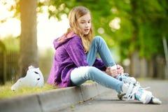 Menina bonita que aprende ao patim de rolo no dia de verão em um parque Capacete de segurança vestindo da criança que aprecia o o fotos de stock royalty free