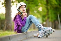 Menina bonita que aprende ao patim de rolo no dia de verão em um parque Capacete de segurança vestindo da criança que aprecia o o fotografia de stock
