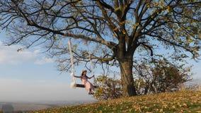 Menina bonita que balança em um balanço sob uma árvore grande filme