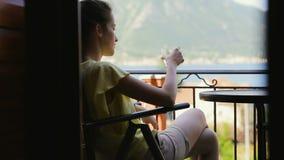 Menina bonita que bebe a água fresca do vidro Viajante fêmea na camisa amarela que aprecia vista surpreendente ao relaxar em video estoque