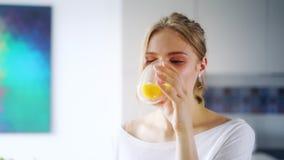 Menina bonita que bebe o suco de laranja fresco do vidro Feche acima da mulher feliz video estoque