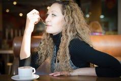 Menina bonita que bebe um cappuccino em um café Fotografia de Stock Royalty Free