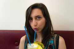 Menina bonita que bebe um cocktail e que olha direta Fotos de Stock Royalty Free