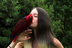 Menina bonita que beija um papagaio Fotografia de Stock Royalty Free