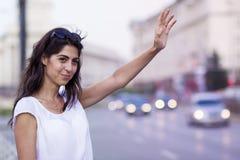 Menina bonita que chama o táxi de táxi Imagem de Stock Royalty Free