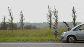 Menina bonita que chama o telefone celular perto de seu carro quebrado em uma estrada secundária filme