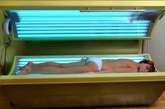 Menina bonita que coloca em um solarium Imagem de Stock