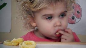 Menina bonita que come com círculos friáveis do milho do prazer vídeos de arquivo