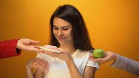 Menina bonita que come a filhós em vez da maçã, apego do açúcar, petisco insalubre vídeos de arquivo