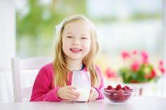 Menina bonita que come framboesas e o leite bebendo em casa Criança bonito que aprecia seus frutos frescos e bagas saudáveis Imagens de Stock Royalty Free