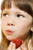 Menina bonita que come a morango saboroso Foto de Stock