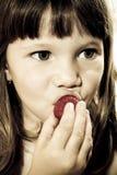 Menina bonita que come a morango saboroso Fotos de Stock