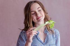 Menina bonita que come o aipo Imagens de Stock Royalty Free