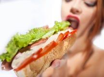 Menina bonita que come o cachorro quente Foto de Stock