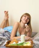 Menina bonita que come o café da manhã na cama Imagens de Stock Royalty Free