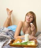 Menina bonita que come o café da manhã na cama Fotos de Stock
