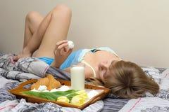Menina bonita que come o café da manhã na cama Fotos de Stock Royalty Free