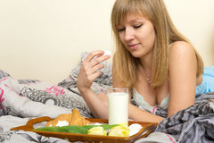Menina bonita que come o café da manhã na cama Imagens de Stock