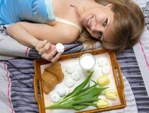 Menina bonita que come o café da manhã na cama Fotografia de Stock