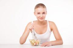 Menina bonita que come a salada de fruto isolada Imagem de Stock