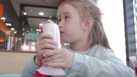 Menina bonita que come um hotdog em um caf? da borda da estrada Fast food no auto conceito do curso video estoque