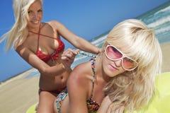 Menina bonita que desata a amiga do swimsuit Fotografia de Stock Royalty Free