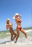 Menina bonita que desata a amiga do swimsuit Fotografia de Stock