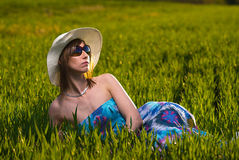 Menina bonita que descansa em um campo da mola Imagens de Stock Royalty Free