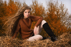 Menina bonita que descansa no pacote da palha Imagem de Stock Royalty Free
