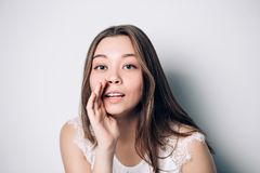 Menina bonita que diz um segredo Mulher feliz nova do retrato Sussurro modelo da menina engraçada sobre algo Foto de Stock Royalty Free