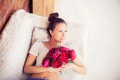 Menina bonita que encontra-se com um ramalhete das flores Imagens de Stock Royalty Free