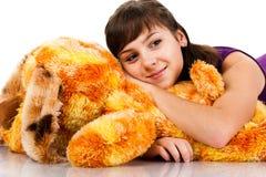Menina bonita que encontra-se em um brinquedo macio Imagens de Stock Royalty Free