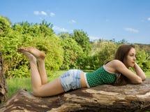 Menina bonita que encontra-se em uma árvore Imagem de Stock