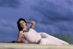 Menina bonita que encontra-se em uma duna de areia Imagens de Stock Royalty Free