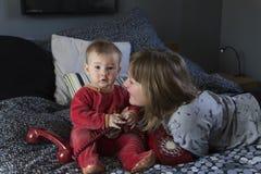 Menina bonita que encontra-se na cama que olha lovingly em sua irmã carnudo bonito do bebê fotos de stock royalty free