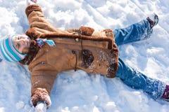 Menina bonita que encontra-se na neve no inverno Fotos de Stock