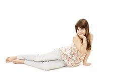 Menina bonita que encontra-se no assoalho nas calças de brim foto de stock