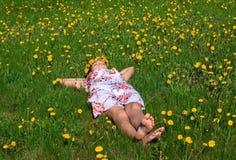 Menina bonita que encontra-se para baixo da grama Fotos de Stock