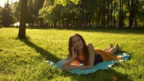 Menina bonita que encontra-se para baixo em um prado e que fala pelo smartphone video estoque