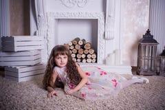 Menina bonita que encontra-se perto da chaminé Fotografia de Stock Royalty Free