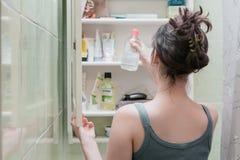 Menina bonita que escolhe produtos de beleza da prateleira do banheiro e para tomá-la imagens de stock royalty free