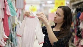 Menina bonita que escolhe a roupa para a posição do bebê perto de uma prateleira da roupa das crianças no supermercado, compra, a filme