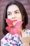 Menina bonita que esconde atrás da folha vermelha do outono um fundo da parede de tijolo Imagem de Stock Royalty Free