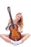 Menina bonita que esconde atrás de uma guitarra Fotografia de Stock Royalty Free
